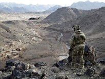A Special Forces soldier observes a valley in Uruzgan as a Blackhawk circles above.