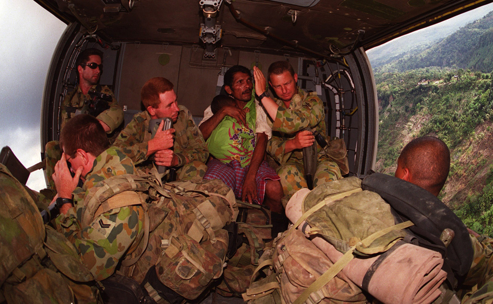 An INTERFET patrol extracted from the mountainous East Timor border region transports an extra passenger to the care of the INTERFET field hospital in Dili.  An INTERFET soldier shields the childs father from the wind as he cradles his young baby, suspected to be suffering from malaria.