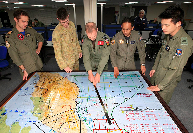 Lieutenant David Roderick from the Royal New Zealand Navy, Lieutenant Lucas Joyce from The Australian Army, Squadron Leader Ady Smith from the Royal Air Force, Captain Ahmad Zaky from the Royal Malaysian Armed Forces and Lieutenat Tan Yit Chong from the Republic of Singapore Air Force go over the day's movements in the Planning Room.