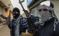 Syrian soldiers, who have defected to join the Free Syrian Army, hold up their rifles as they secure a street in Saqba, in Damascus suburbs, in this January 27, 2012