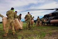 Soldiers load boxes of pillows, blankets and towels onto a Black Hawk helicopter to be transported from Rockhampton to Theodore. The Black Hawk helicopter is from the 5th Aviation Regiment, Townsville, working as part of the Joint Task Force (JTF) 637 Operation QUEENSLAND FLOOD ASSIST.