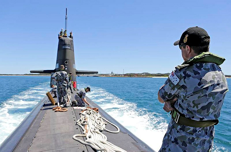 Petty Officer Electronic Warfare Submarines Bradley Smith on the submarine casing onboard HMAS Dechaineux as the boat departs from Diamantina Wharf at Fleet Base West.