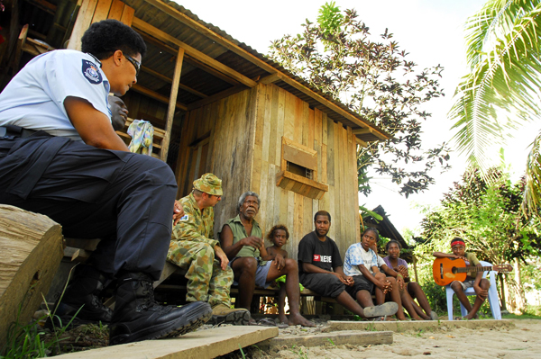 Fijian Participating Police Force advisor Lait Buakula and Warrant Officer Class Two Graham Bell listens in as locals sing for them in a village on the outskirts of Honiara.