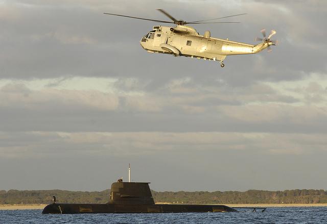 HMAS Manoora's SK50 Sea King helicopter flies over Collins Class submarine, HMAS Collins.