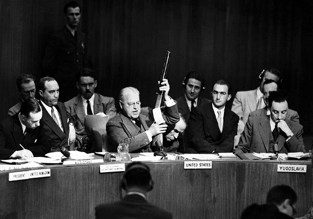 At U.N. Security Council, Warren Austin, U.S. delegate, holds Russian-made submachine gun dated 1950, captured by American troops in July 1950. He charges that Russia is delivering arms to North Koreans.