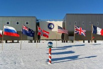 Amundsen-Scott South Pole Station in the 2007–2008 summer season. The new elevated Amundsen-Scott South Pole Station is now complete. In the foreground is the ceremonial South Pole and the flags for the original 12 signatory nations to Antarctic Treaty.