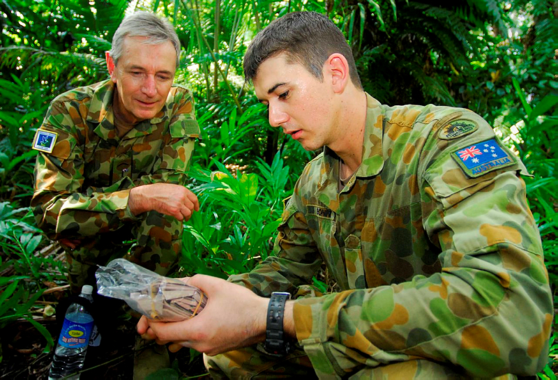Private Marcus Bonini shows Liberal Senator Nick Minchin the contents of a ration pack 'in the field' during a visit to Solomon Islands.