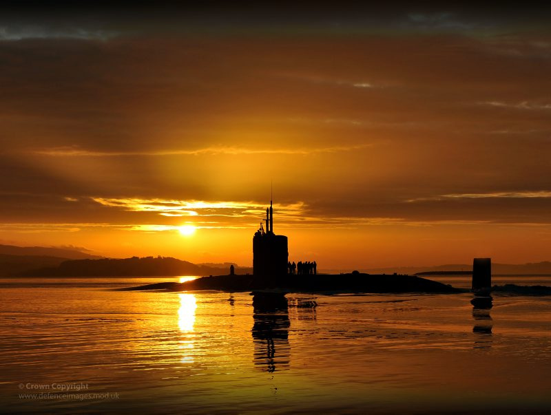 The Royal Navy's HMS Triumph, a Trafalgar Class nuclear submarine, glides into HM Naval Base Clyde in the early morning sun following a patrol