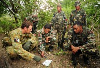 Captain Paul Sanderson with the Defence Co-operation Program (DCP) checks the navigation on a map with an East Timor Defence Force (F-FDTL) section from the Ready Company Group.