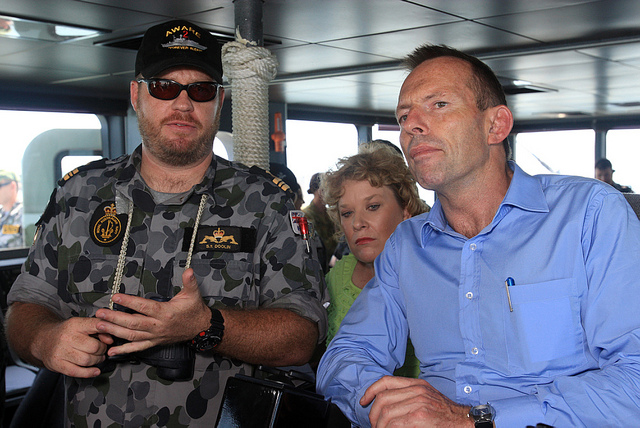 Lieutenant Commander Shane Doolin, Commanding Officer of Aware Two explains the equipment on the bridge to the Hon Tony Abbott MP and Mrs Natasha Griggs MP prior to departure from HMAS Coonawarra basin on board HMAS Glenelg.