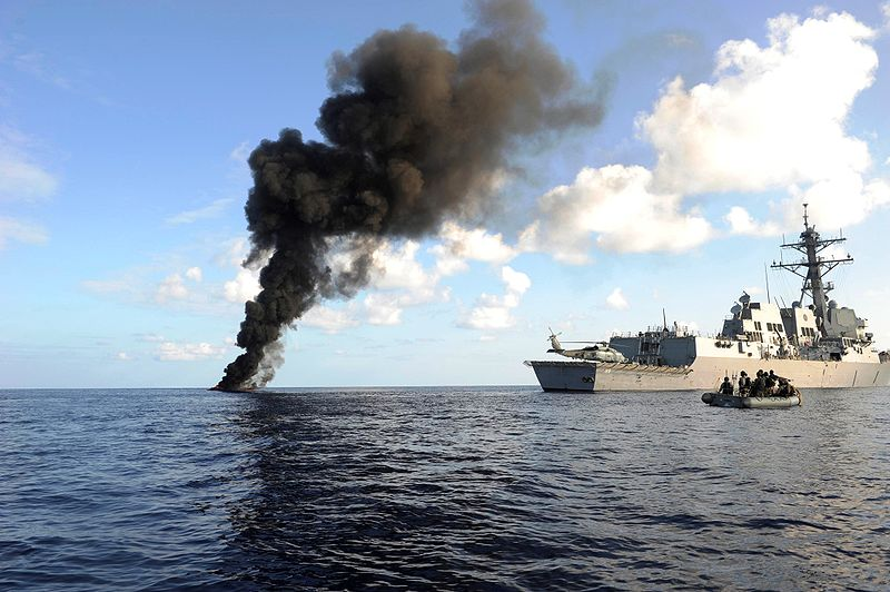 The Arleigh Burke-class guided missile destroyer USS Farragut (DDG 99) passes by the smoke from a suspected pirate skiff it had just destroyed. USS Farragut is part of Combined Task Force 151, a multinational task force established to conduct anti-piracy operations in the Gulf of Aden.