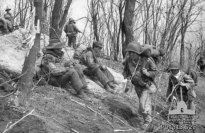 Hill Salmon, Korea, 1951-04-17. Carrying heavy loads on their backs, soldiers (right) of K Company, 19th Regimental Combat Team (RCT), 6th Republic of Korea (ROK) Infantry Division, arrive on Hill Salmon to relieve C Company, 3rd Battalion, The Royal Australian Regiment (3RAR). Two Australian soldiers (left) are sitting on the ground with their packs on their backs, ready to move out. The ROKs abandoned the hill to Chinese forces when they attacked a few days later. (Donor I. Robertson)