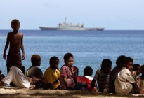 Lambi village children gather on the beach to see the rare sight of HMAS Manoora anchored in Lambi Bay. Some of the villagers took to small craft to take closer look at the warship in their sheltered bay.