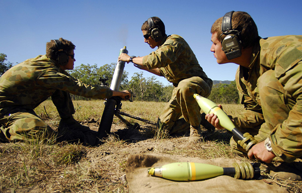 From left: Private (PTE) Chris Redman, PTE Michael Crank and PTE Frank Attard from mortar platoon, 2nd Battalion, The Royal Australian Regiment, prepare to fire during a live practice at Shoalwater Bay Training Area.