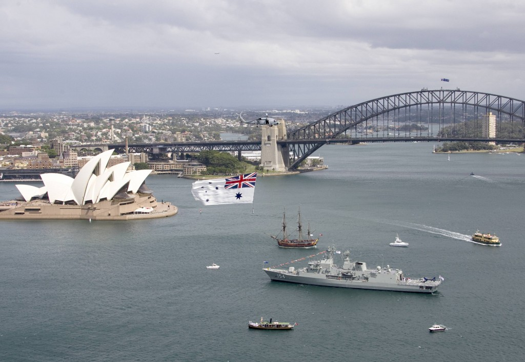 A Navy Seahawk helicopter from 816 Squadron, flys the Australian White Ensign over Sydney Harbour while Chief of Navy Vice Admiral Ray Griggs, AO CSC, RAN launches the Royal Australian Navy's International Fleet Review 2013 on board HMAS Parramatta in Sydney Harbour.
