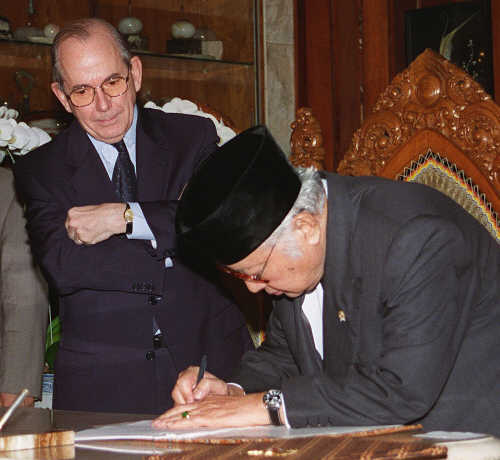 President Suharto signing an emergency loan agreement with the International Monetary Fund, and then IMF head Michel Camdessus