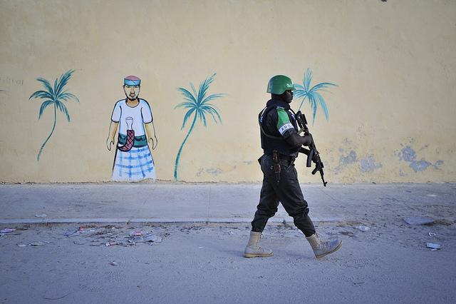 A Nigerian policeman walks by a newly built wall on a foot patrol near Lido beach in Somalia's capital, Mogadishu.