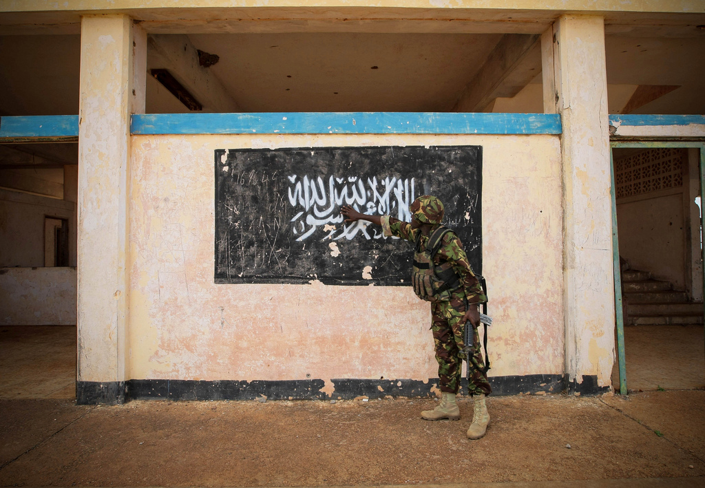 A soldier of the Kenyan Contingent serving with the African Union Mission in Somalia (AMISOM) gestures towards the black flag of the Al Qaeda-affiliated extremist group Al Shabaab painted on the wall of Kismayo Airport.