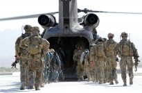 Australian Special Forces soldiers and Afghan National Police Special Response Team members board an American Chinook helicopter at the airfield in Tarin Kot.