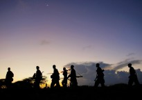 "Soldiers of the Somali National Army (SNA) walk at dusk under a rising crescent moon near the outskirts of Afgooye, a town to the west of Somali capital Mogadishu. On the third day of the SNA's joint offensive with the African Union Mission in Somalia (AMISOM), dubbed ""Operation Free Shabelle"", troops have advanced to almost two kilometres outside the strategically important town, having captured along the way swathes of territory previously under the control of the Al Shabaab insurgent group. Photo ID 515019. 24/05/2012. Somalia. UN Photo/Stuart Price"