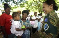 Corporal Aspen Williams gives local children presents for Christmas in a small village on the out skirts of Honiara in the Solomon Islands.