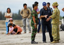 AusAID's Sam Zappia talks with Flying Officer Mick McGirr and an Indonesian military official on the beach of Pariaman.