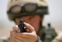 A British soldier aims a Browning 9mm pistol on a shooting range at Basra, Iraq