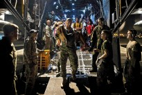 Families from Ormoc affected by Typhoon Haiyan exit an MC-130 Combat Talon II from 1st Special Operation Squadron (1 SOS) after being transported as part of Operation Damayan