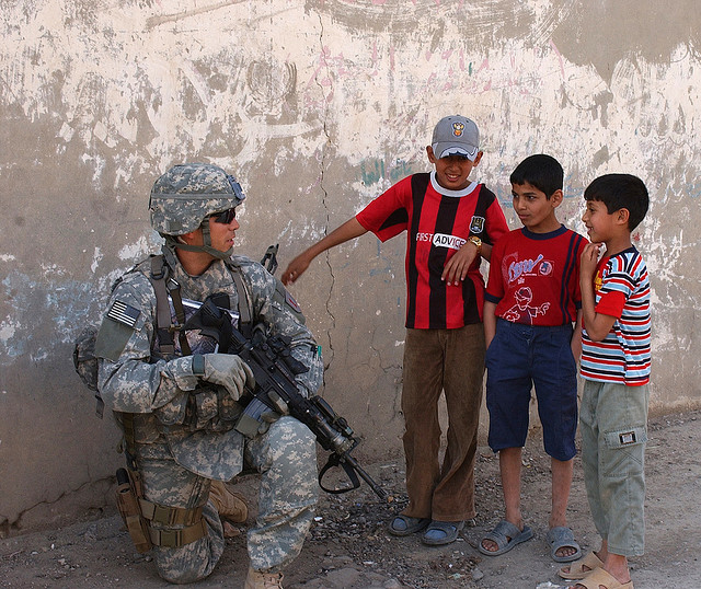 U.S. Army Staff Sgt. Robert Montez, with Alpha Company, 2nd Battalion, 16th Infantry Regiment, 2nd Brigade Combat Team, 1st Infantry Division, speaks with local kids during a patrol through the Mashtal area of East Baghdad, Iraq, March 13, 2007. (U.S. Army photo by Spc. Davis Pridgen) www.army.mil