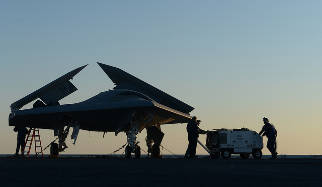 Northrop Grumman personnel conduct preoperational tests on a U.S. Navy X-47B Unmanned Combat Air System demonstrator aircraft on the flight deck of the aircraft carrier USS George H.W. Bush (CVN 77) May 14, 2013, in the Atlantic Ocean. The George H.W. Bush was the first aircraft carrier to successfully catapult-launch an unmanned aircraft from its flight deck. (DoD photo by Mass Communication Specialist 2nd Class Timothy Walter, U.S. Navy/Released)