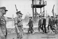 Bien Hoa, South Vietnam. June 1970. The Chief of Staff of the Headquarters Australian Force Vietnam, Colonel (Col) J. Whitelaw, passes a group of prisoners of war (POWs) during his inspection of the III Corps POW cage. Col Whitelaw presented a small library to the camp. He was accompanied on his inspection by the Vietnamese commandant, Major Sanh Qui.