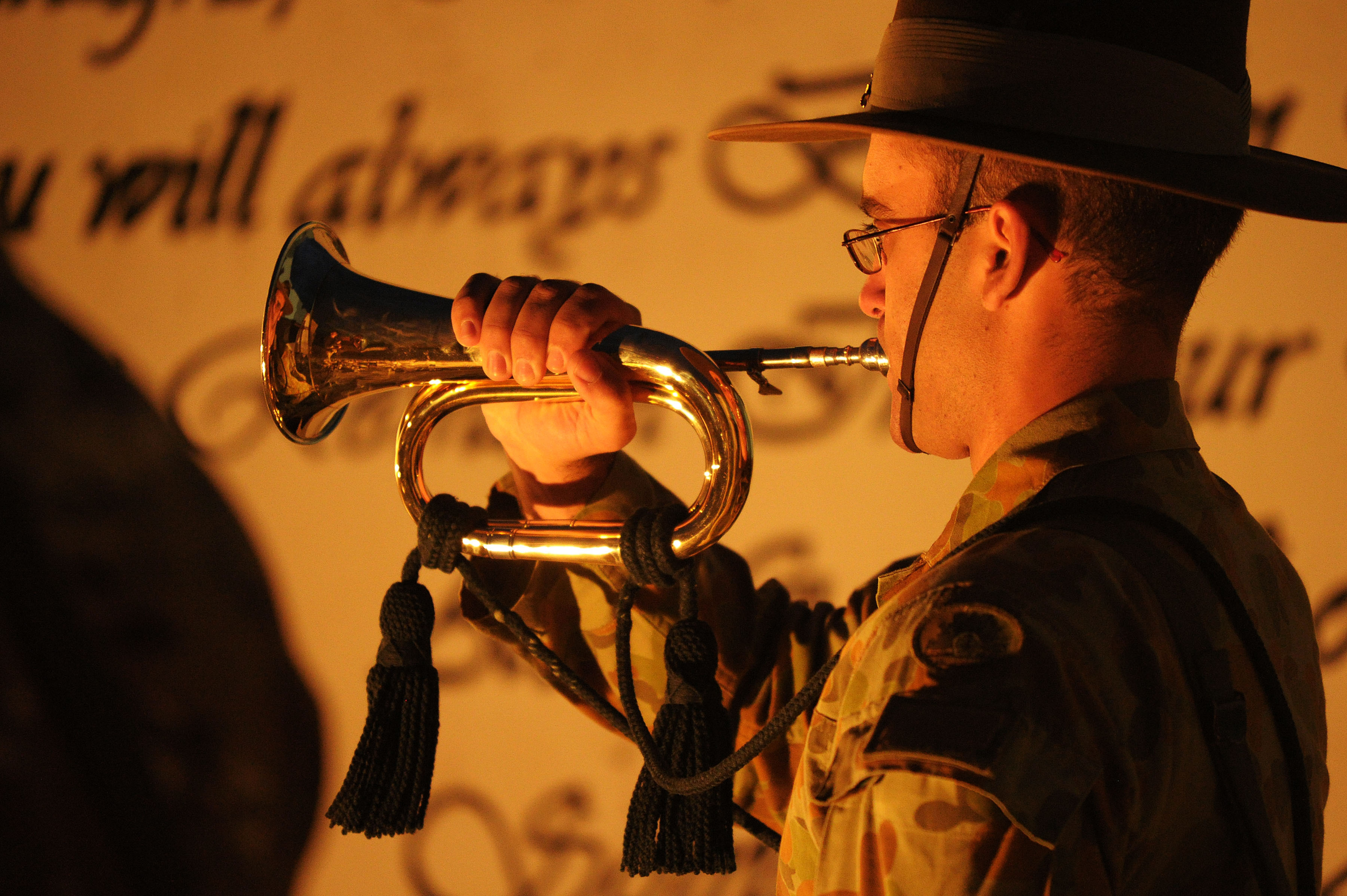 Bugler Corporal James Duquemin from the Band of the Royal Military College Duntroon plays the Last Post during the Anzac Day Dawn Service at Multi National Base – Tarin Kot.