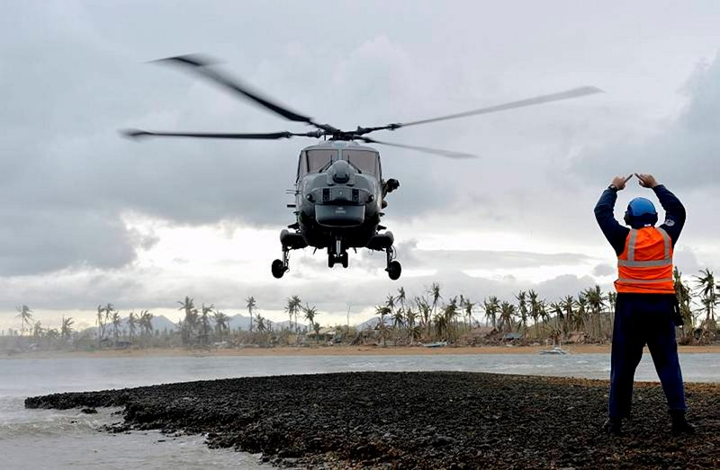 HMS Daring's Lynx helicopter arrives on the typhoon stricken Philippine island of Binuluanguan.  Sailors from HMS Daring have continued their efforts to deliver aid to the victims of Typhoon Haiyan in the Philippines.