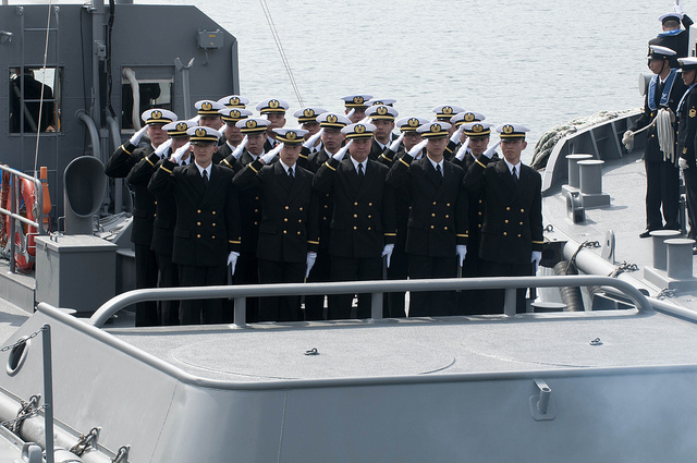 Graduates of the Japan Maritime Self-Defense Force (JMSDF) Officer Candidate School salute their instructors and family members as they prepare to sail off to their prospective ships.