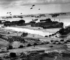 """Landing ships putting cargo ashore on one of the invasion beaches, at low tide during the first days of the Normandy invasion, June 1944. Among identifiable ships present are USS LST 532 (in the centre of the view); USS LST 262 (third LST from right); USS LST 310 (second LST from right); USS LST 533 (partially visible at far right); and USS LST 524. Note the barrage balloons overhead and the Army """"half-track"""" convoy forming up on the beach."""