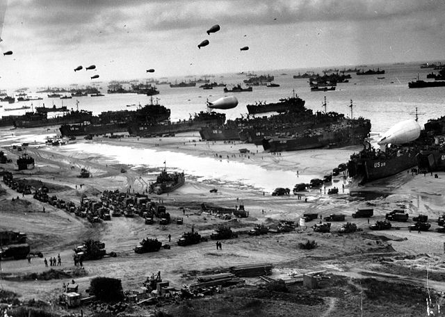 "Landing ships putting cargo ashore on one of the invasion beaches, at low tide during the first days of the Normandy invasion, June 1944. Among identifiable ships present are USS LST 532 (in the centre of the view); USS LST 262 (third LST from right); USS LST 310 (second LST from right); USS LST 533 (partially visible at far right); and USS LST 524. Note the barrage balloons overhead and the Army ""half-track"" convoy forming up on the beach."