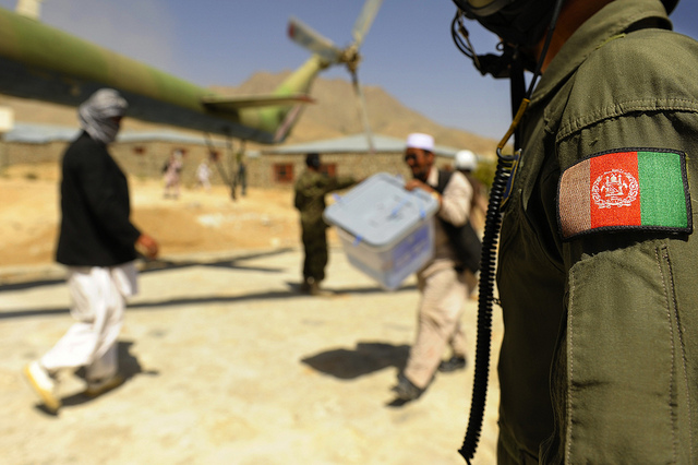 An Afghan National Air Force member looks on as civilians load ballot boxes into an Mi-17 helicopter in Jaghuri, Afghanistan, Sept. 20, 2010.