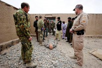 Australian Defence Force Investigative Service Sergeant Ben Gilbey (left) and Australian Federal Police Sergeant Nathan Thompson watch as Afghan National Police and Criminal Investigation Division members work a crime scene during Evidence Based Police Operations training held at Multi National Base - Tarin Kot, Afghanistan.