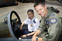 Commanding Officer No. 3 Squadron Wing Commander Timothy Alsop shows Director, Defence Planning and Policy Department, Major General Yoshinara Marumo, ASO, from the Japan Air Self-Defence Force throughout the cockpit of an F/A-18 hornet.