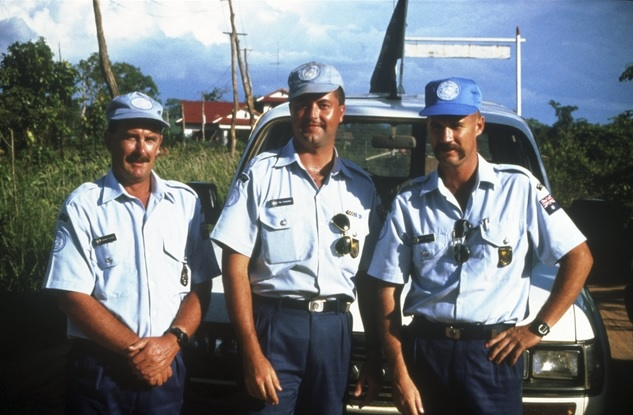 Three police officers serving with the United Nations Transitional Authority in Cambodia (UNTAC). Their role was to help maintain order before and during the national elections. The men are all wearing blue United Nations (UN) caps.