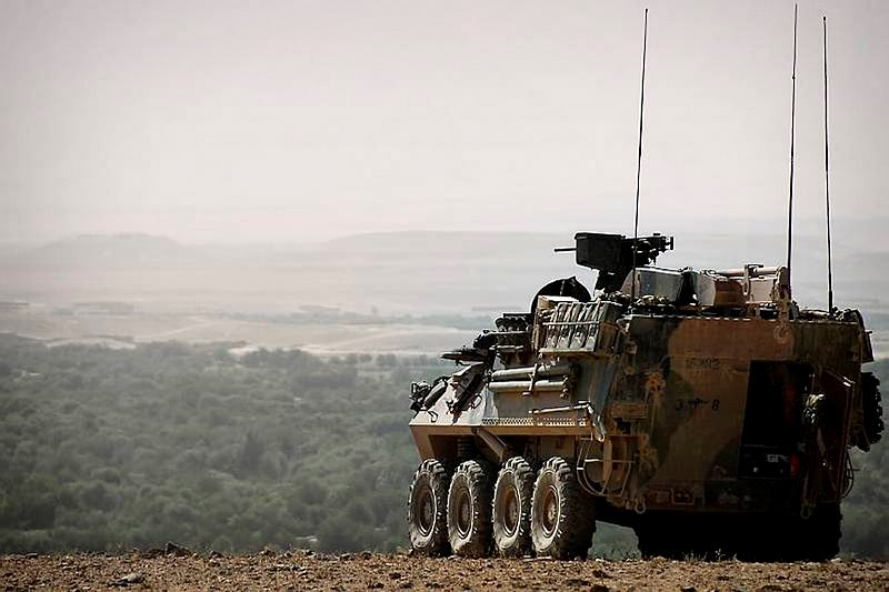 "An Australian Light Armoured Vehicle positioned to provide over watch for an infatry platoon patrolling through the ""green zone"" below."