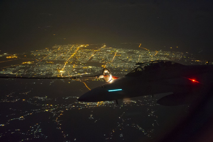 A Royal Australian Air Force (RAAF) F/A-18F Super Hornet aircraft makes contact with the fuel hose of a RAAF KC-30A Multi Role Tanker Transport aircraft above a city in Iraq.