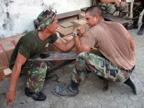 Utilitiesman 3rd Class Orestes Chavez and an Indonesian Marine take a break from placing tile in an Indonesian elementary school to arm wrestle.