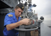 A Russian sailor assigned to the Russian navy destroyer RFS Admiral Chabanenko (DD 650) plots a course