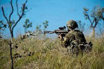 An Australian Army soldier from A Company, the 3rd Battalion, The Royal Australian Regiment fires an F88 Austeyer at an enemy position during a live fire exercise at the 3rd Brigade Combined Arms Training Activity.