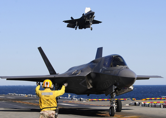 An aviation boatswain's mate maneuvers BF-04, front, the U.S. Marine Corps variant of the F-35B Lighting II