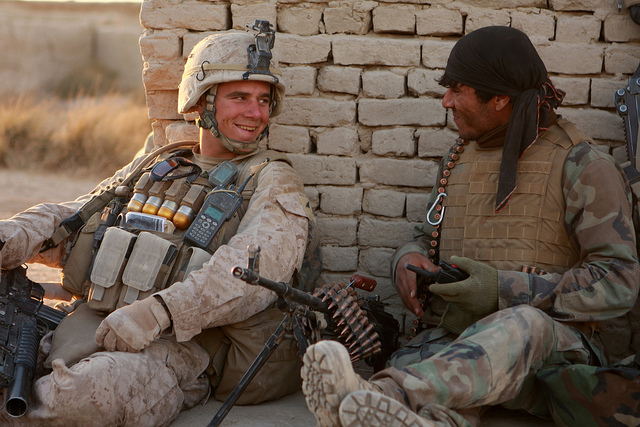 Afghan National Army soldier Taza Khan hands a bag of beef jerky to a local boy, injured by an improvised explosive device, while patrolling with U.S. Marines from 3rd Platoon, Lima Company, 3rd Battalion, 3rd Marine Regiment during Operation Tageer Shamal (Shifting Winds)  on 5 January 2012.