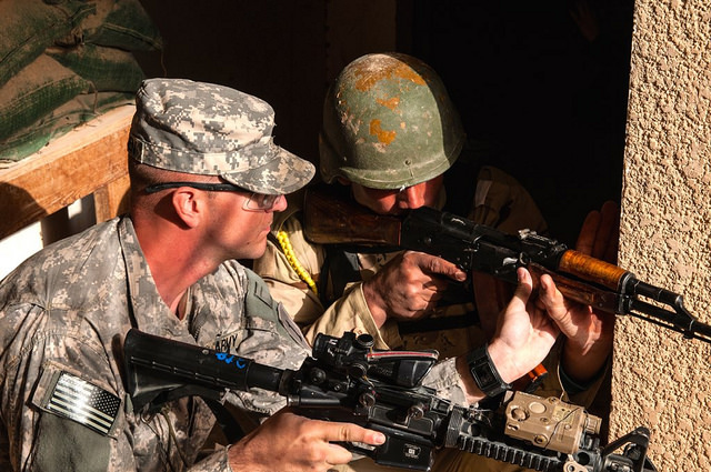 A U.S. Army Soldier assigned to 1st Armored Brigade Combat Team, 1st Infantry Division, adjusts an Iraqi trainee's weapon to ensure he's covering the correct sector of fire during infantry squad tactical training lanes, Jan. 7, 2015, at Camp Taji, Iraq. U.S. Army photo by Master Sgt. Mike Lavigne