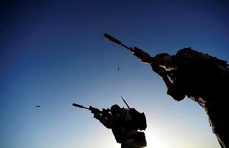 Spent cartridiges eject from a Special Operations Task Group (SOTG) soldiers' M4 rifles as they reconfirm their zeroes prior to a night mission with the Uruzgan Special Response Team (SRT).