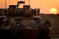 An Australian Light Armoured Vehicle (ASLAV), stands in the light of sunset.